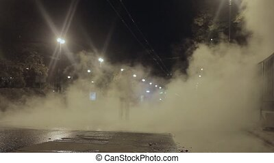 Man walk toward camera in night city street covered in steam from drain accident