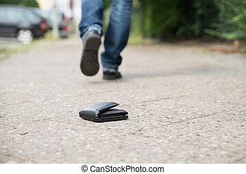 Man Walking Against Fallen Wallet On Street - Low section of...