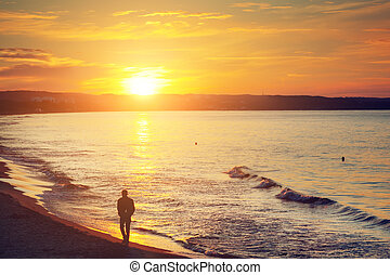 Man walking alone on the beach at sunset. Calm sea with...