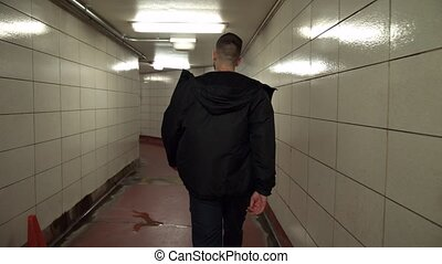 Man walking alone through a tunnel in the Chicago Underground.