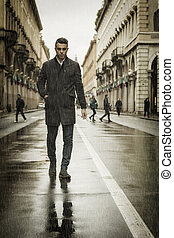 Man walking along rainy street