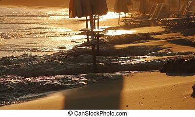 man walking along the beach at suns
