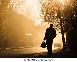 Man walking along the road, backlit at sunset