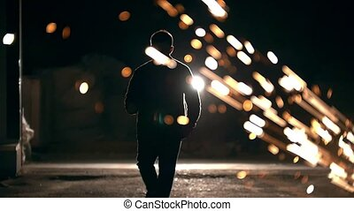 Man walking among the flying sparks from grinder at night,...