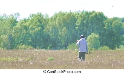 Man walking around with a golf stick on his shoulder on the summer field