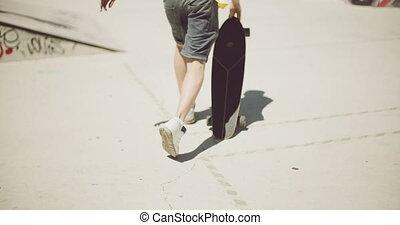 Man walking at a skate park with his skateboard - Man...