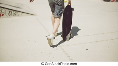 Man walking at a skate park with his skateboard