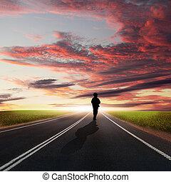 Man walking away at dawn along road - Collage with a human ...