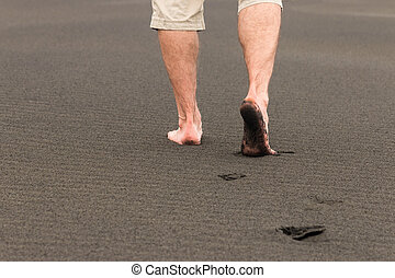 man walking barefoot on sand