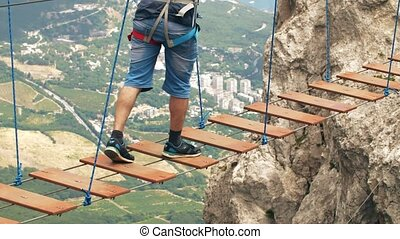 Man walking by suspension bridge - Man walking by dangerous...