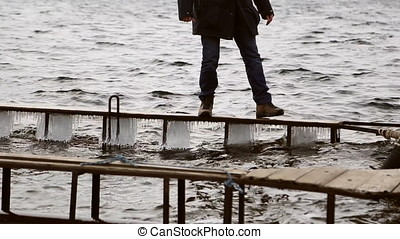 Man walking dangerously on a narrow icy pier on the river in...