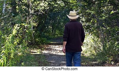 Man walking down a tree lined path