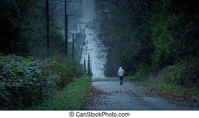 Man Walking Down Hill In The Evening