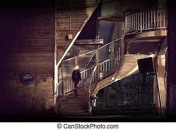 Man walking down staircase in run down area