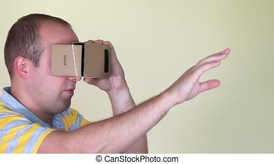 man walking forward with vr virtual reality cardboard glasses