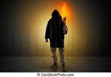 Man walking in an empty space with burning flambeau
