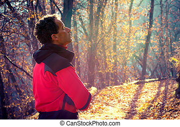 Man walking in autumn forest - Man breathing pure aire and...