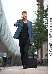 Man Walking in City with Cell and Suitcase
