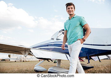 Man walking in field near private aircraft