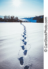 man walking in snow footprints
