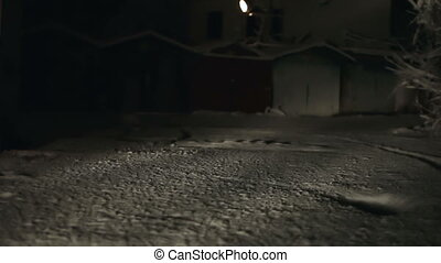 man walking in the snow at night