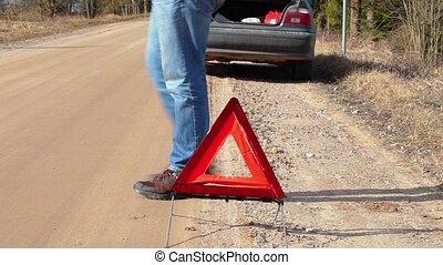 Man walking near warning triangle