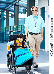 Man walking next to little boy in wheelchair outside medical...