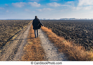 Man walking on a country road in Ukrainian rural area