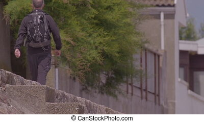 Man walking on a sidewalk past a bush