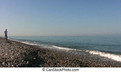 man walking on beach and throws stone into sea
