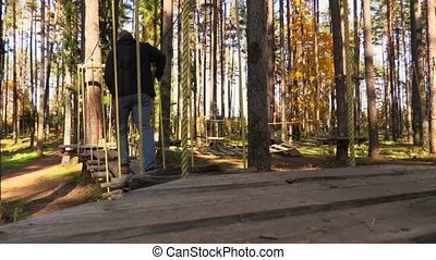 Man walking on cables between trees