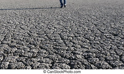 Man walking on dry cracked land - Man in jeans and boots...