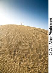 man walking on dunes in the desert