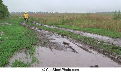 Man walking on muddy dirt road with puddles in rain