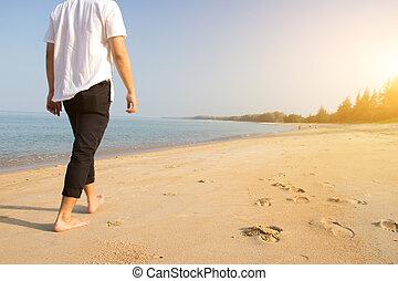 man walking on ocean beach