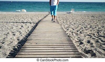 Man walking on pier in beach