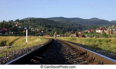 Man walking on railroad in mountains
