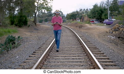Man walking on railroad tracks while using his smart phone -...