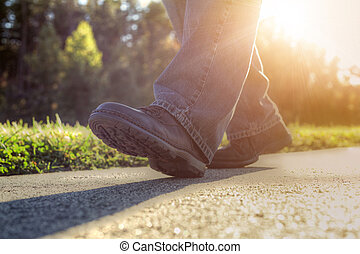 Man walking on road. - Close up of a man walking on road.
