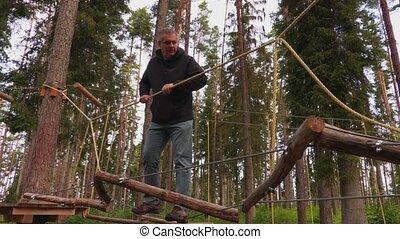 Man walking on rope bridge in park