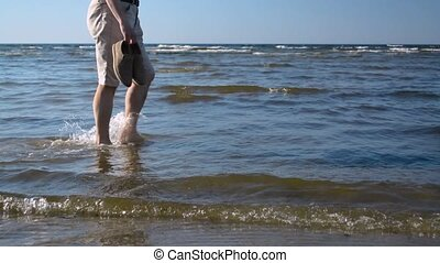 Man walking on shallow water from left to right by the sea...