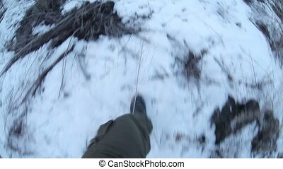 man walking on snow and dry grass journey legs in boots close-up video gopro