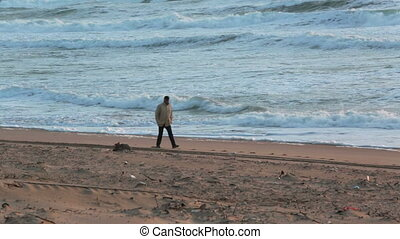 Man walking on the beach with storm
