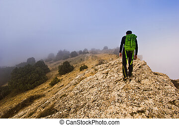 man walking on the edge of a cliff in foggy weather
