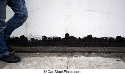 Man walking on the street, focus on legs