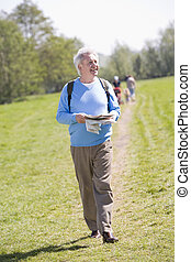 Man walking outdoors holding map smiling with people in backgrou