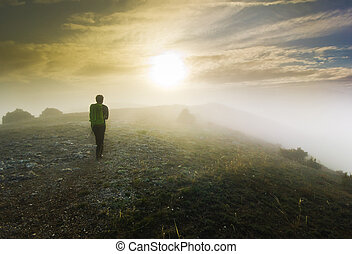 man walking over a hill in foggy weather at sunset