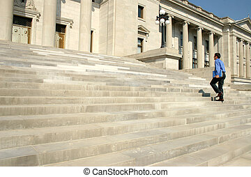 Man Walking Steps - Young adult male walking up steps of a...
