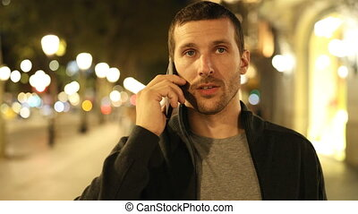 Man walking talking on phone in the night - Front view of a ...