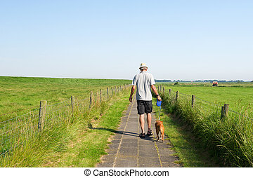 Man walking the dog in summer landscape